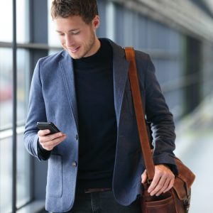 Man messaging in airport on a cell phone