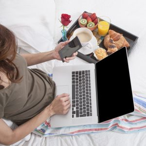 Woman sitting in a hotel bed messaging on a smart phone